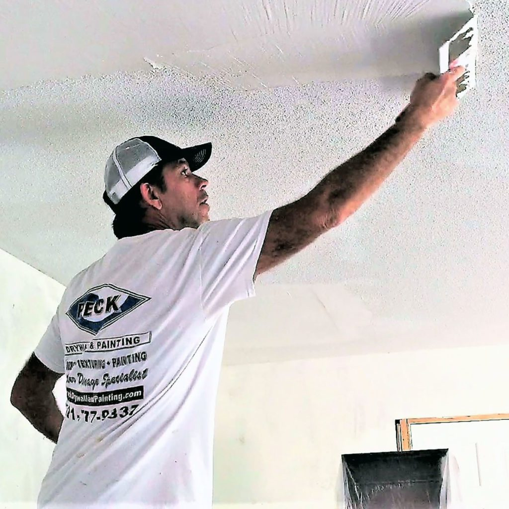 Man applying skim coating to a ceiling   Construction Pro Tips