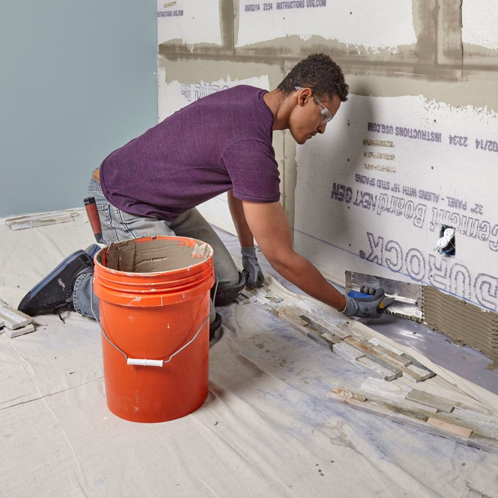 Spread thin-set along the bottom part of the wall | Construction Pro Tips