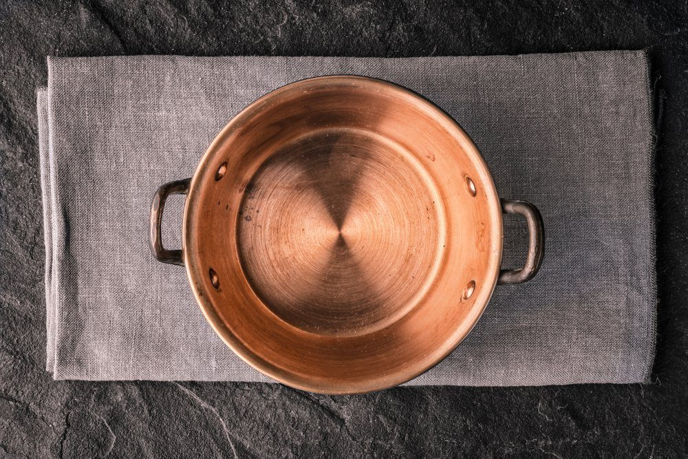 Copper pot on the dark stone table top view