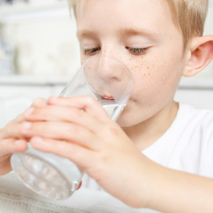 drinking a glass of water at home