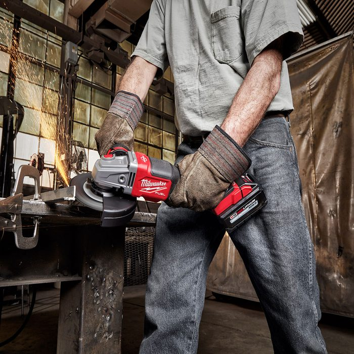 Man grinding metal with a cordless milwaukee grinder | Construction Pro Tips