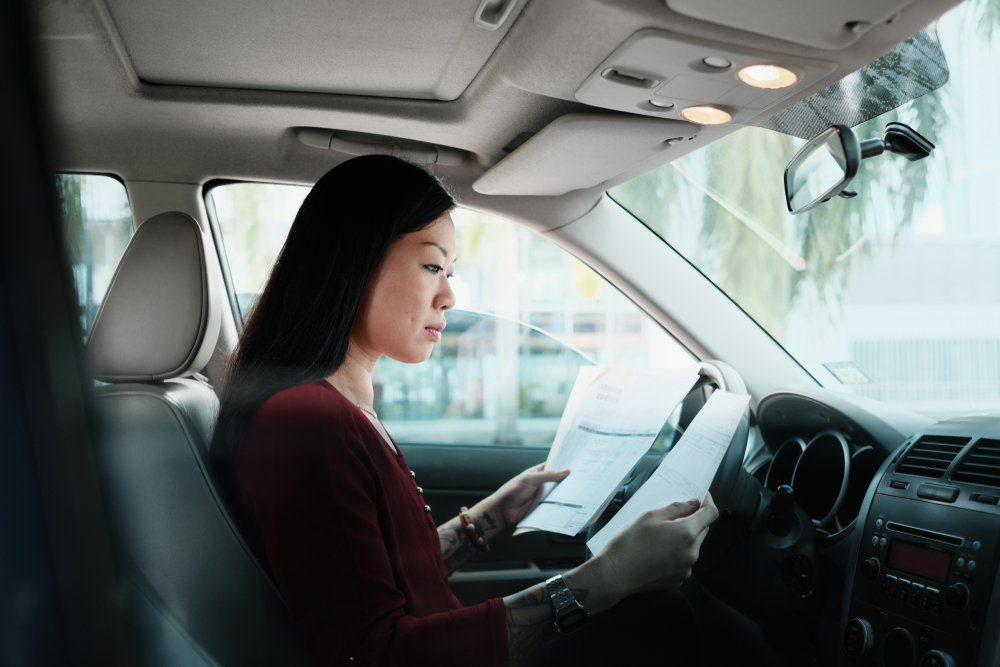 Chinese female manager working in car. Successful Asian businesswoman using laptop computer and looking at paperwork.
