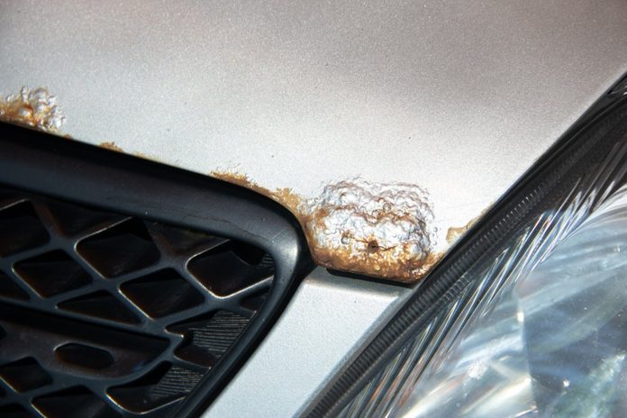 Rust on the bonnet of a silver car with black radiator grille