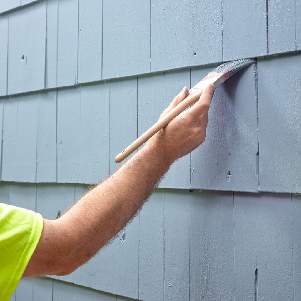 brushing paint on to siding | Construction Pro Tips