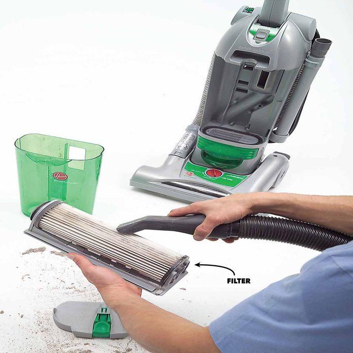 man vacuums a vacuum filter
