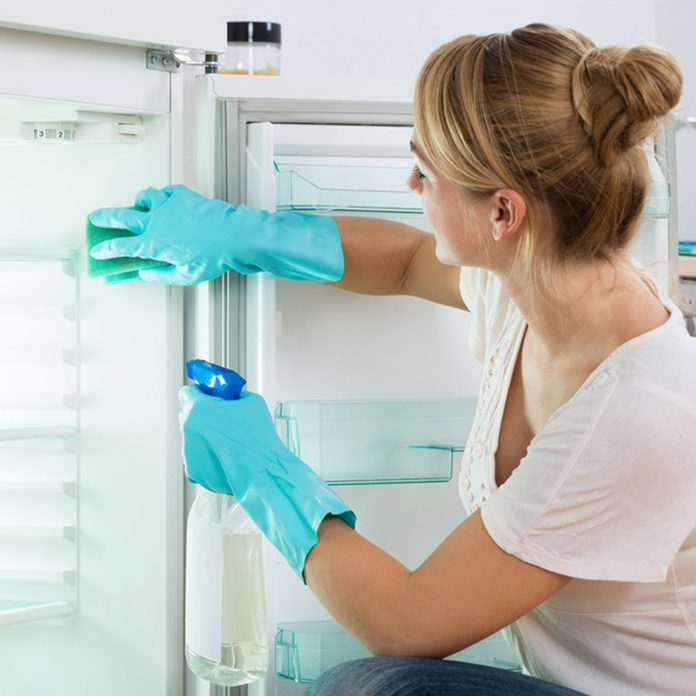 Young woman cleaning refrigerator with sponge and spray at home; Shutterstock ID 338967302