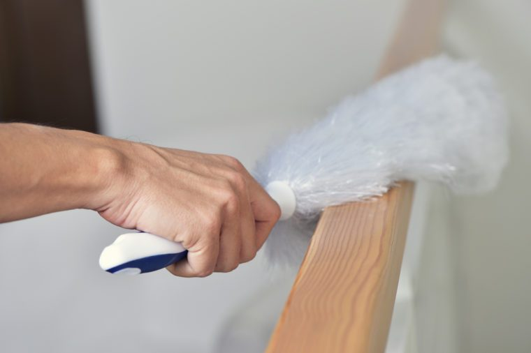 closeup of a young man dusting the house with a white microfiber duster