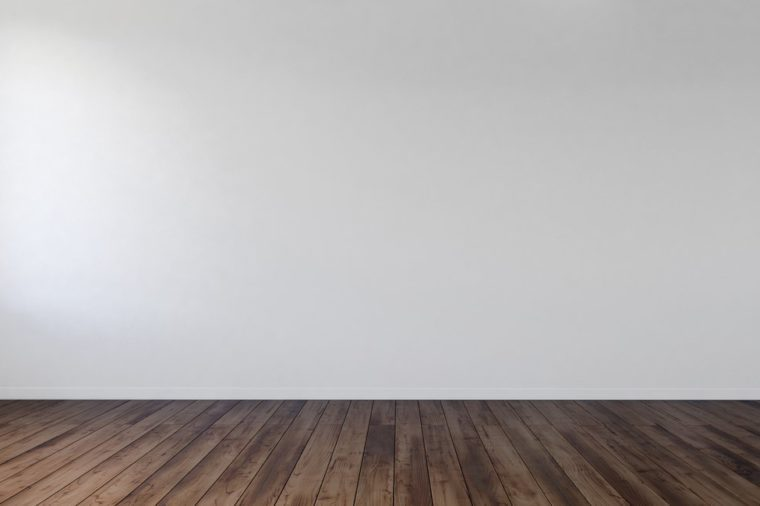 Empty unfurnished bare room interior with white wall and wood floorboards in an architectural background. 3d Rendering.