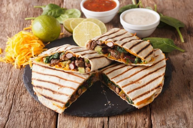 Mexican quesadilla with spinach, beans and cheddar cheese close-up on the table. horizontal