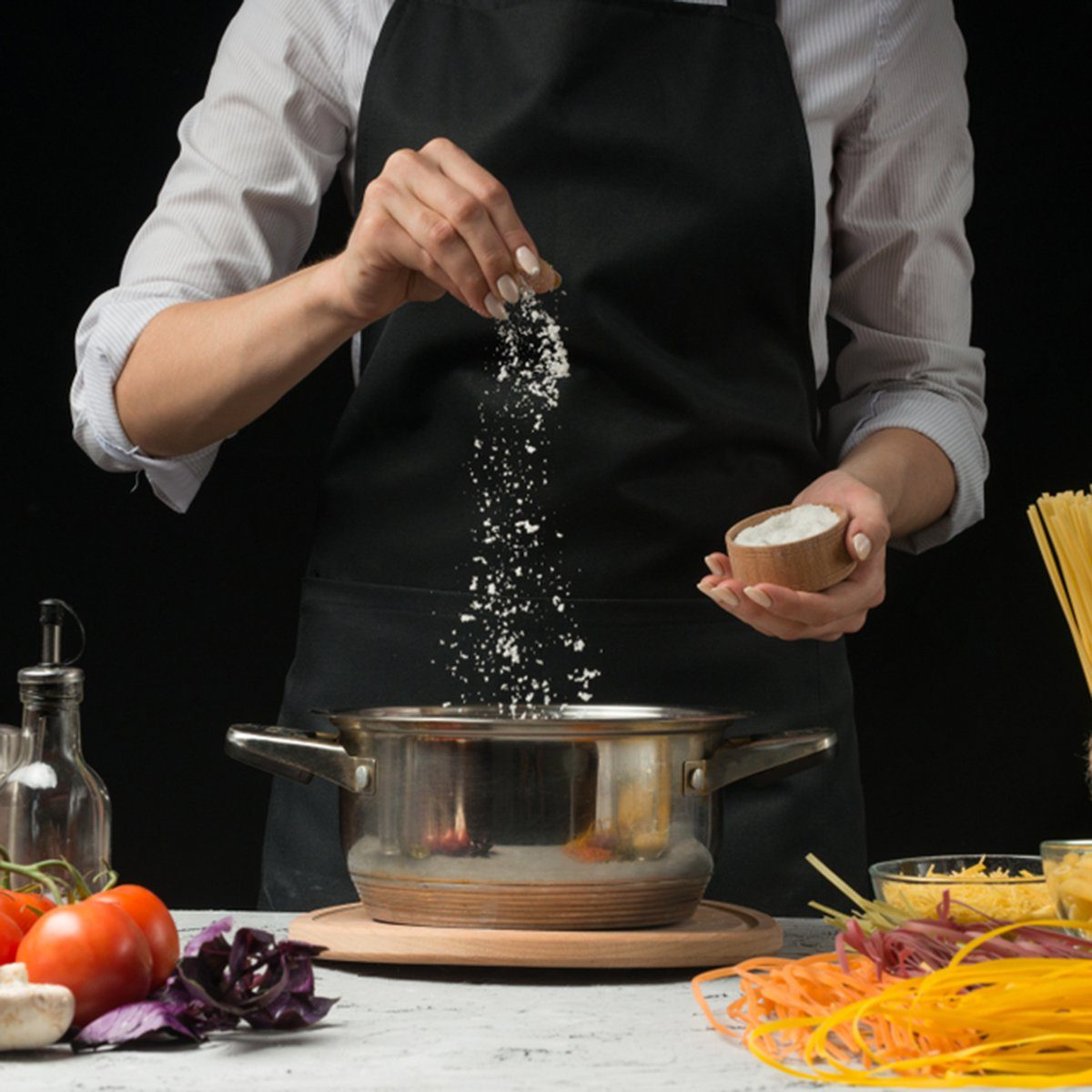 The chef prepares spaghetti and pasta, salt water, against a dark background