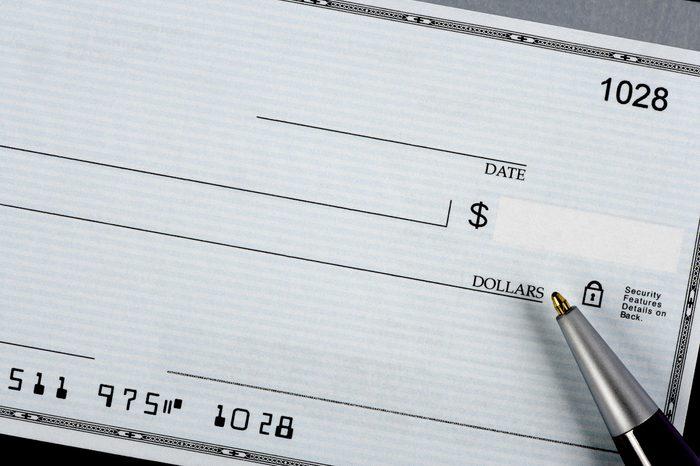 A closeup of a bank check with a pen.