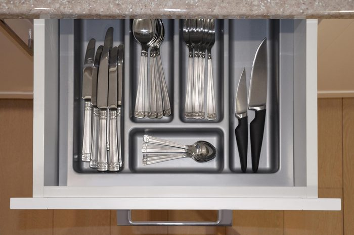 Opened kitchen drawer with a tray and cutlery set with spoons, knife and fork inside. View from above. Image