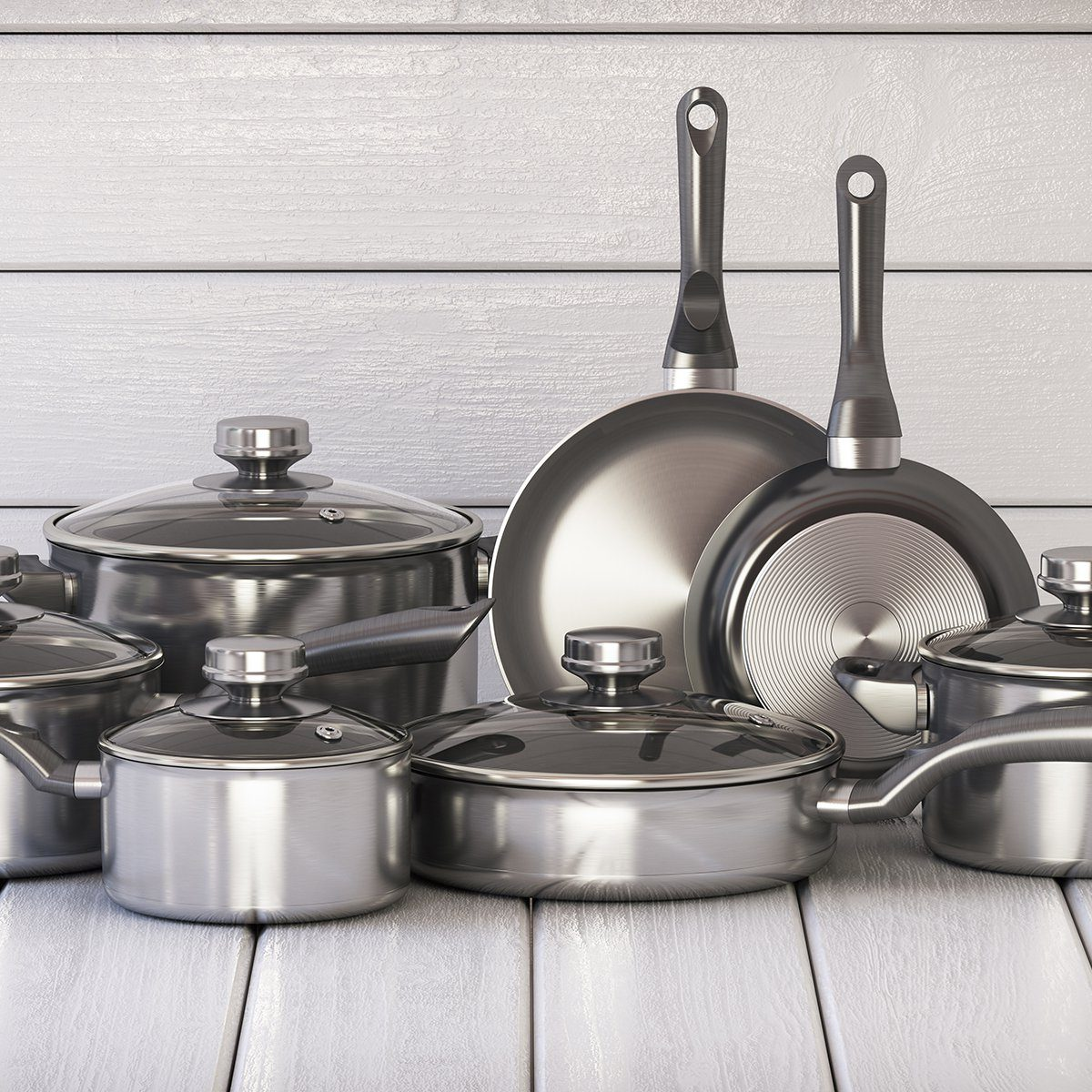 Set of stainless pots and pan with glass lids on the white wooden background
