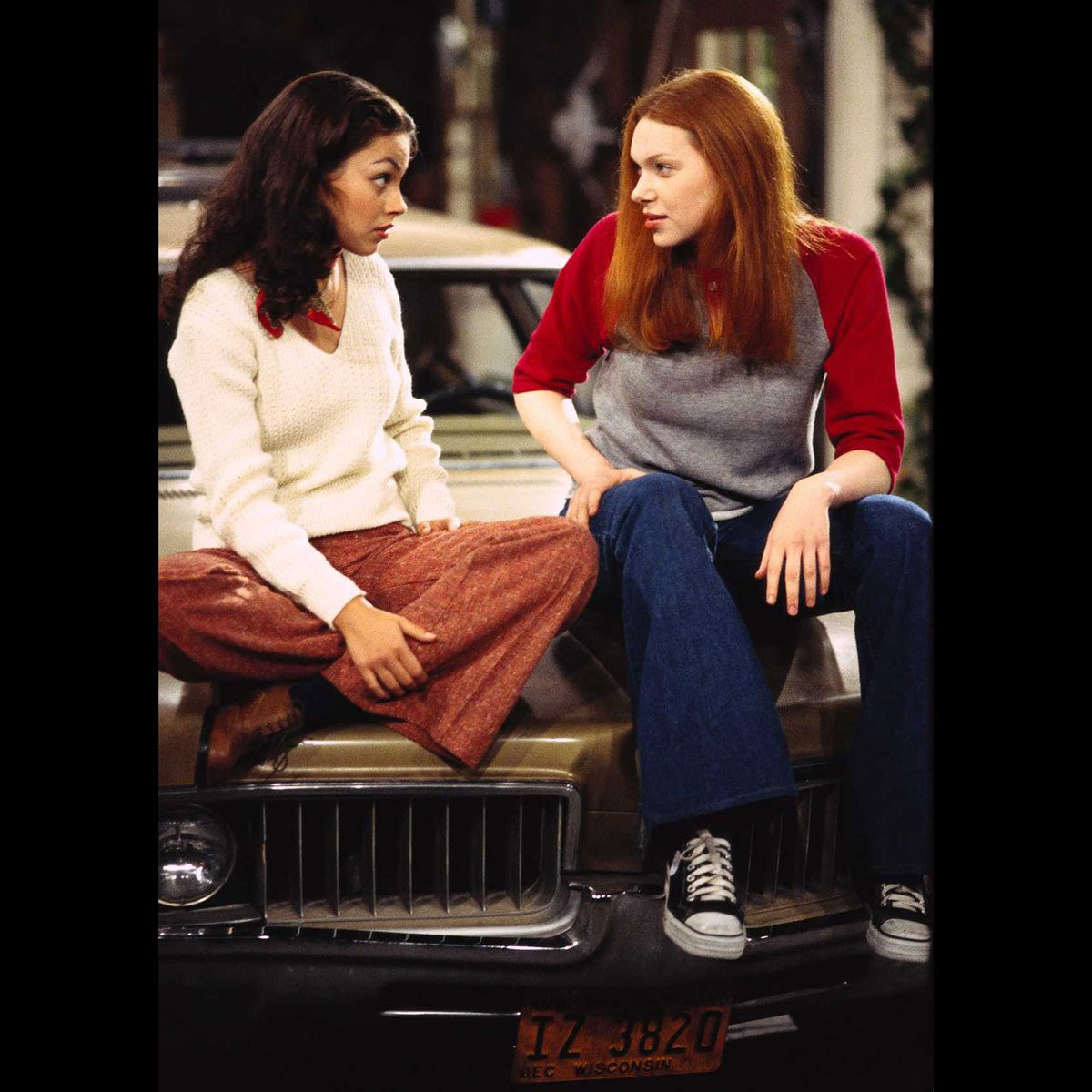 """Mila Kunis and Laura Prepon sit on the hood of a 1969 Oldsmobile Vista Cruiser on the set of """"That '70s Show"""""""