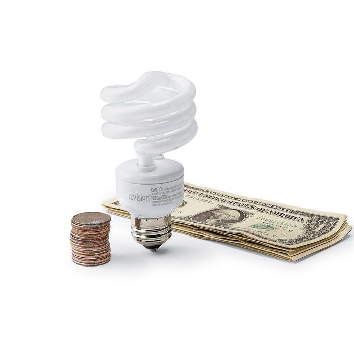 CFL lightbulb between coins and dollar bills
