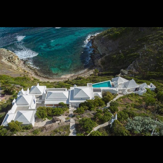 cliff-side mansion that overlooks an ocean bay in the caribbean