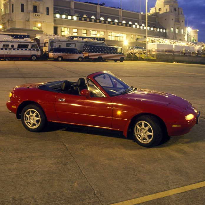 Mazda Miata parked in a parking lot just after dusk with its top down