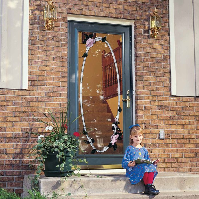 little girl sits with a book on concrete steps in front of a new exterior door