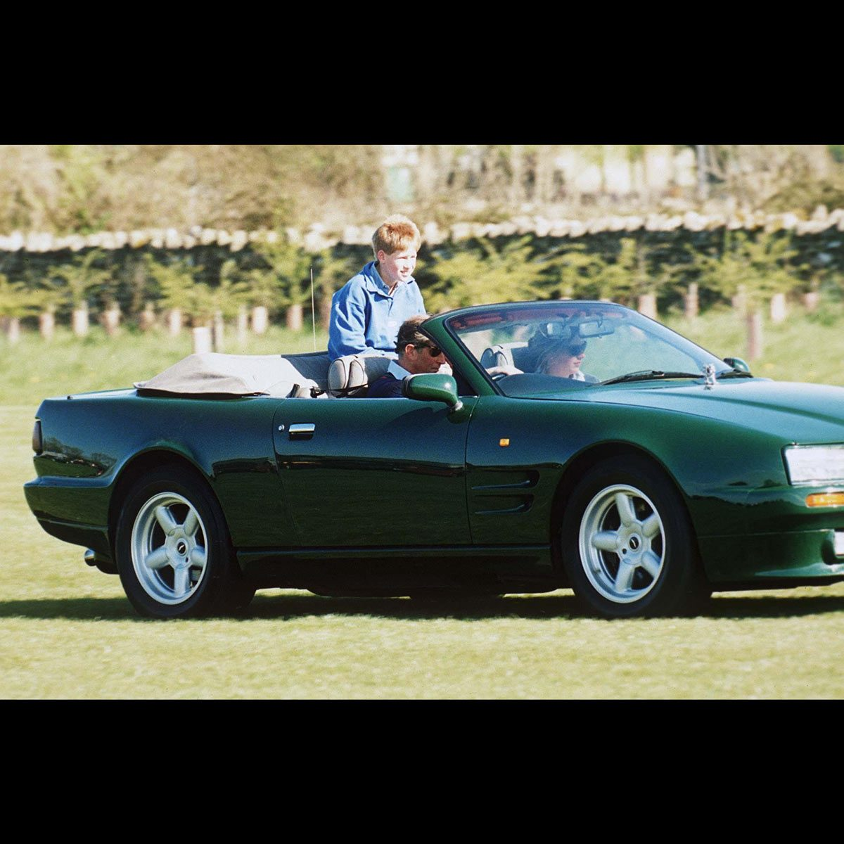 Prince Charles driving Aston Martin convertible car with Tiggy Legge Bourke and Prince Harry riding in the back
