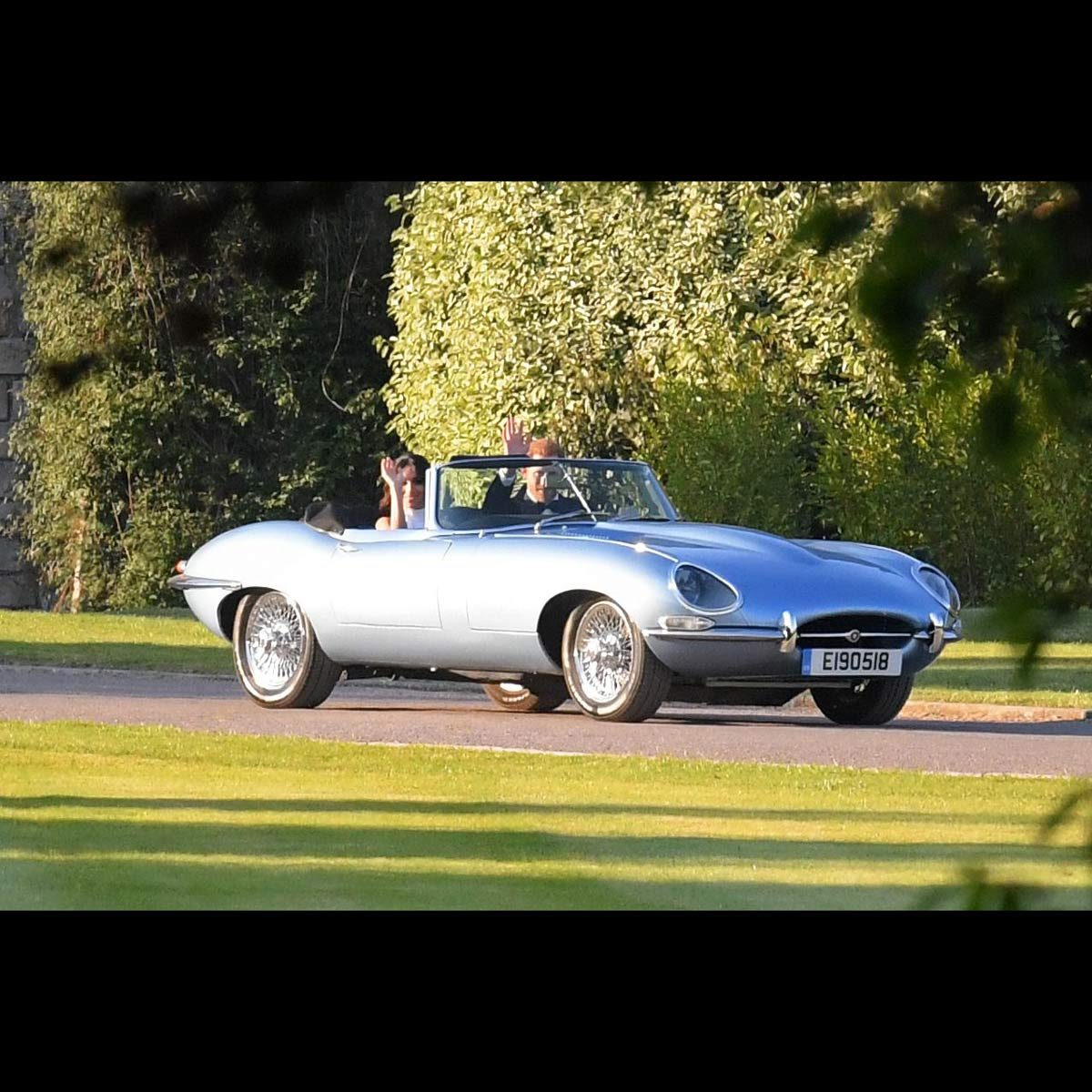 Prince Harry and Meghan Markle wave as they drive away in a Jaguar E-type following their wedding