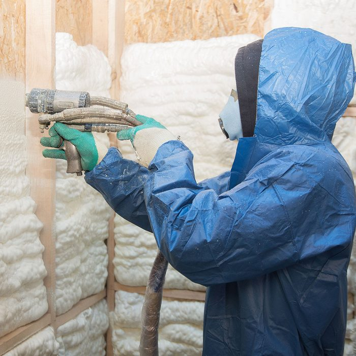 Man applies spray foam insulation
