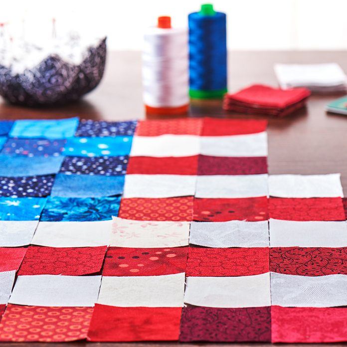 Preparing to sewing of pieces of fabrics that look like a flag of USA