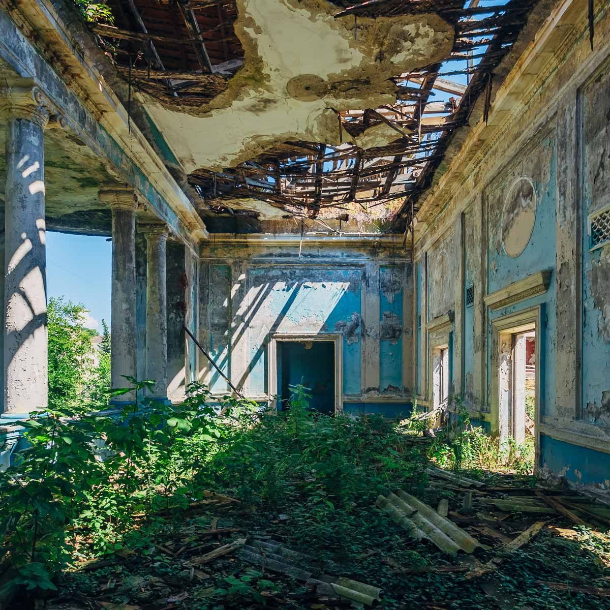 Ruined-abandoned-mansion-overgrown-with-weeds