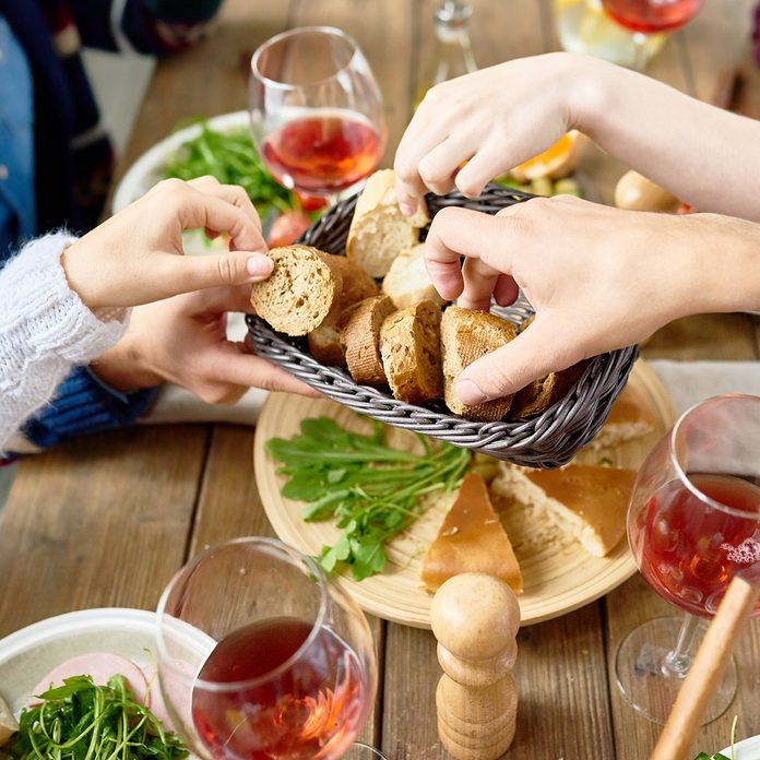 Closeup of unrecognizable people passing bread basket around at festive dinner table
