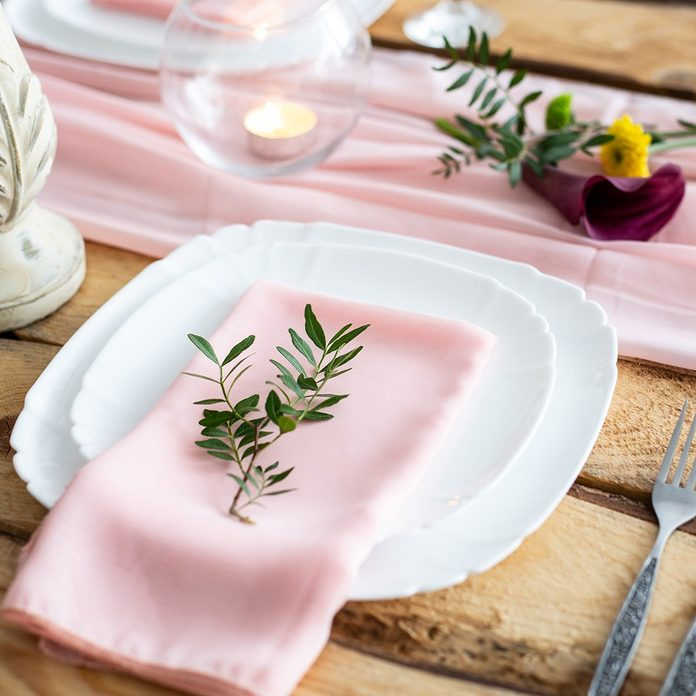 Rustic table setting: pink napkin folded on a plate, next to a champagne glass