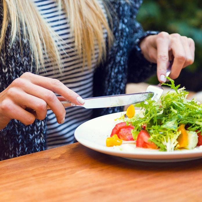 Blonde woman eating green healthy tasty eco salad on city street terrace