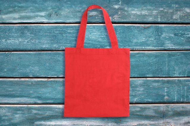 Red tote bag on blue wooden vintage background or texture