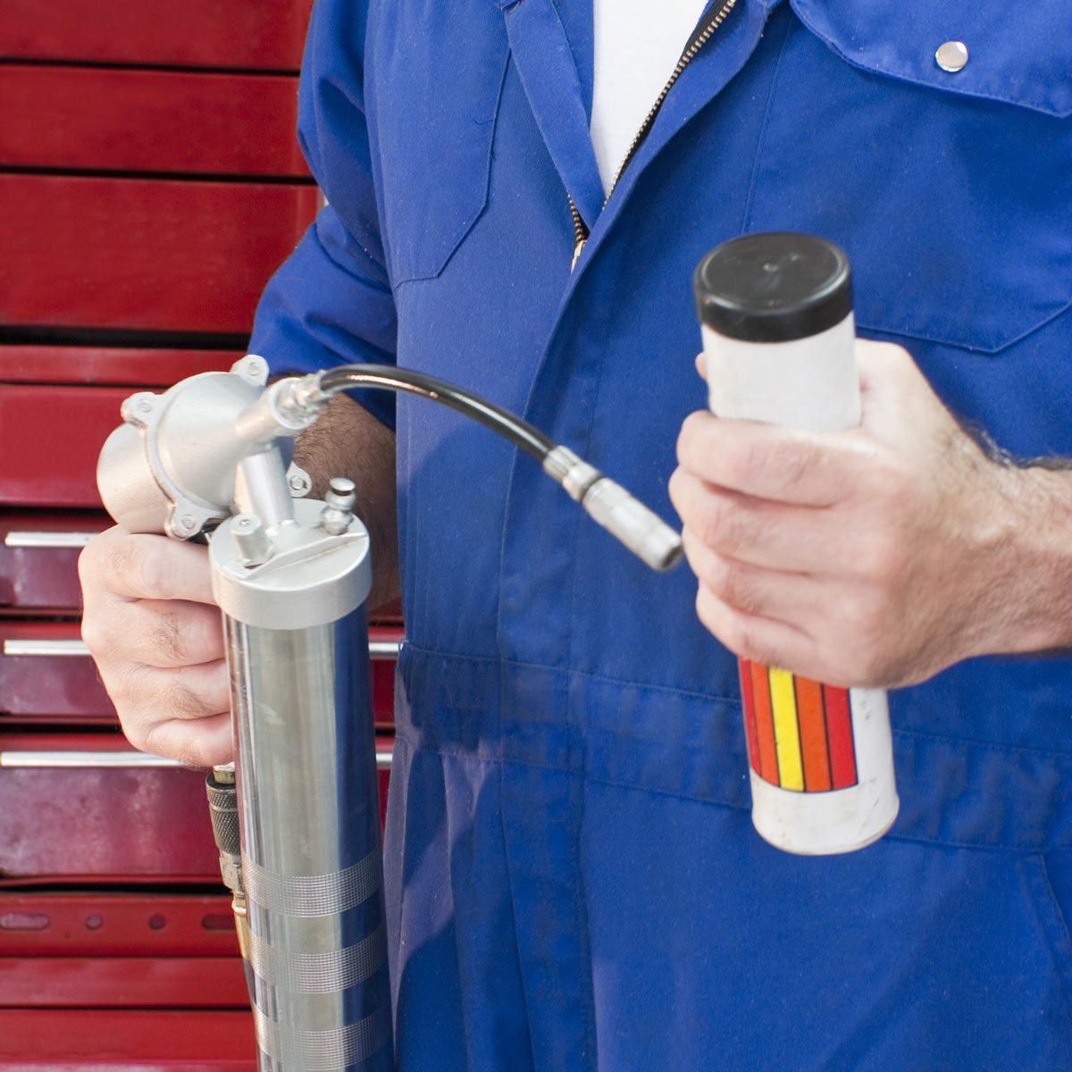 Mechanic-with-grease-gun-.-Auto-repair-shop-service