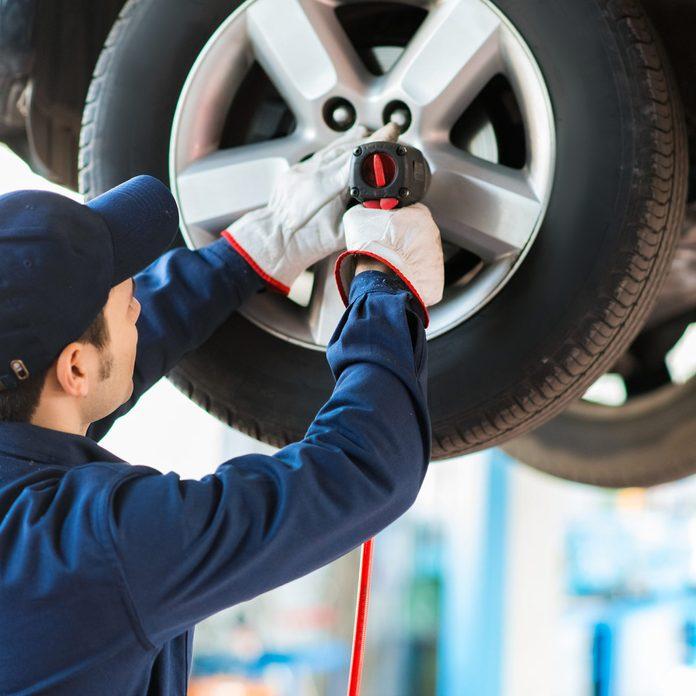 Mechanician-changing-car-wheel-in-auto-repair-shop