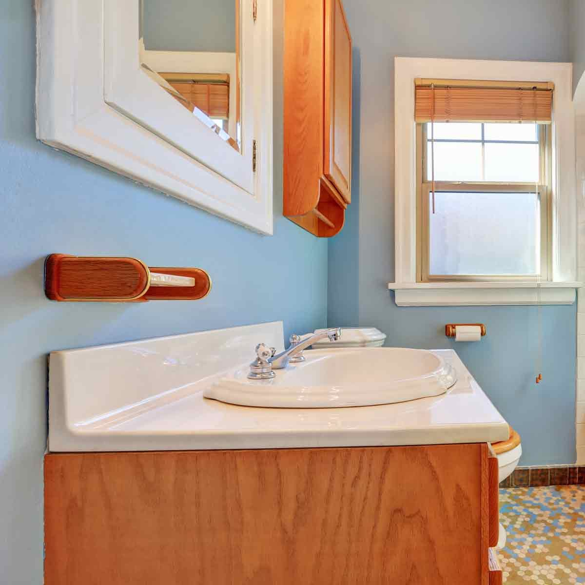 Pale-blue-colorful-bathroom-interior-with-old-fashioned-ceramic-appliances-in-tudor-style-home