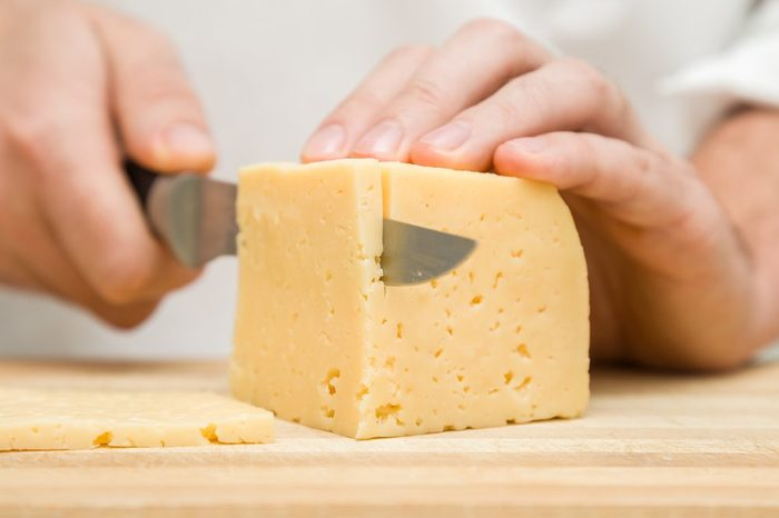 Chef's hands with knife cutting a cheese on the wooden board for sandwich, italian pizza or snack in the kitchen. Preparation for cooking. Healthy eating and lifestyle. Food concept.