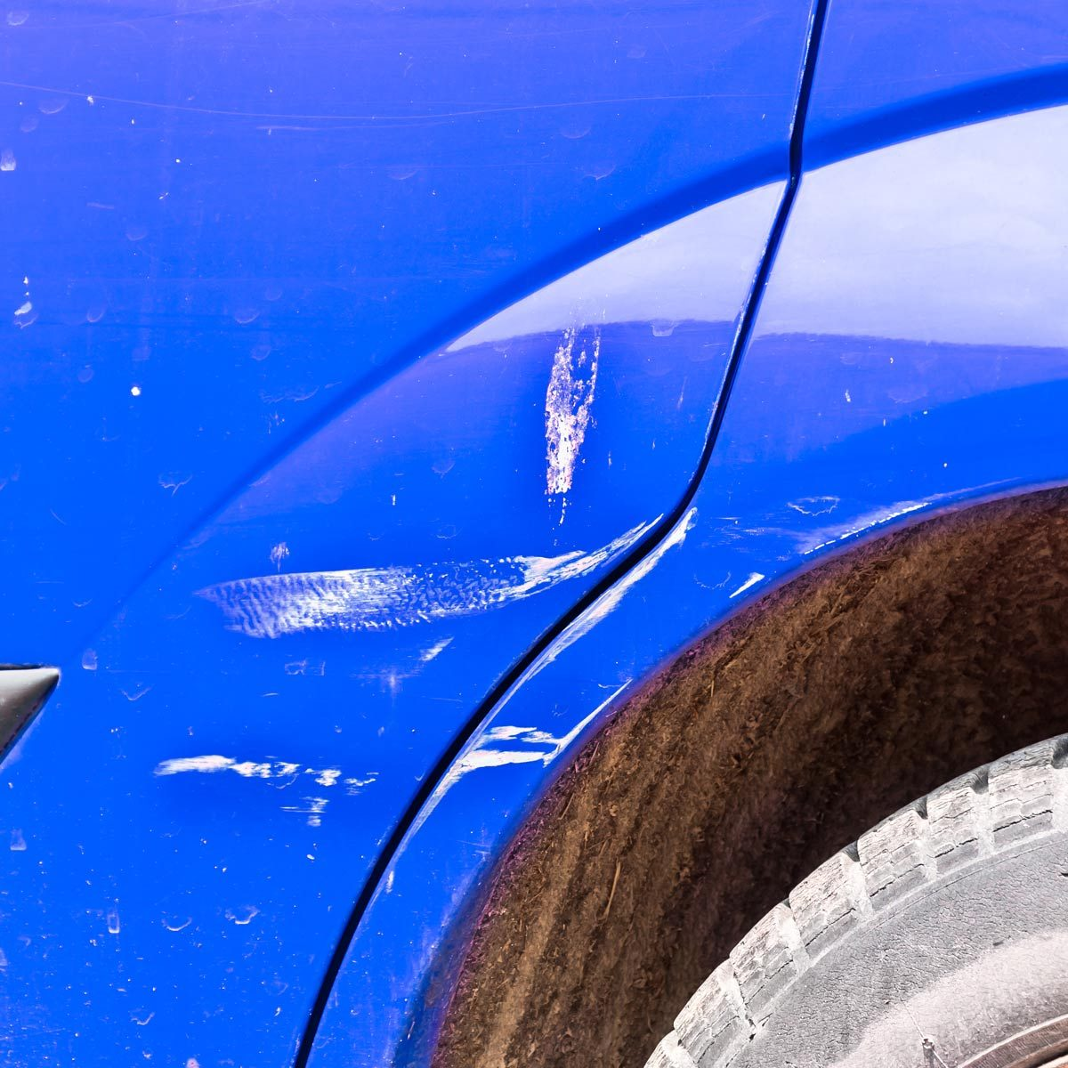 Blue scratched car with damaged paint