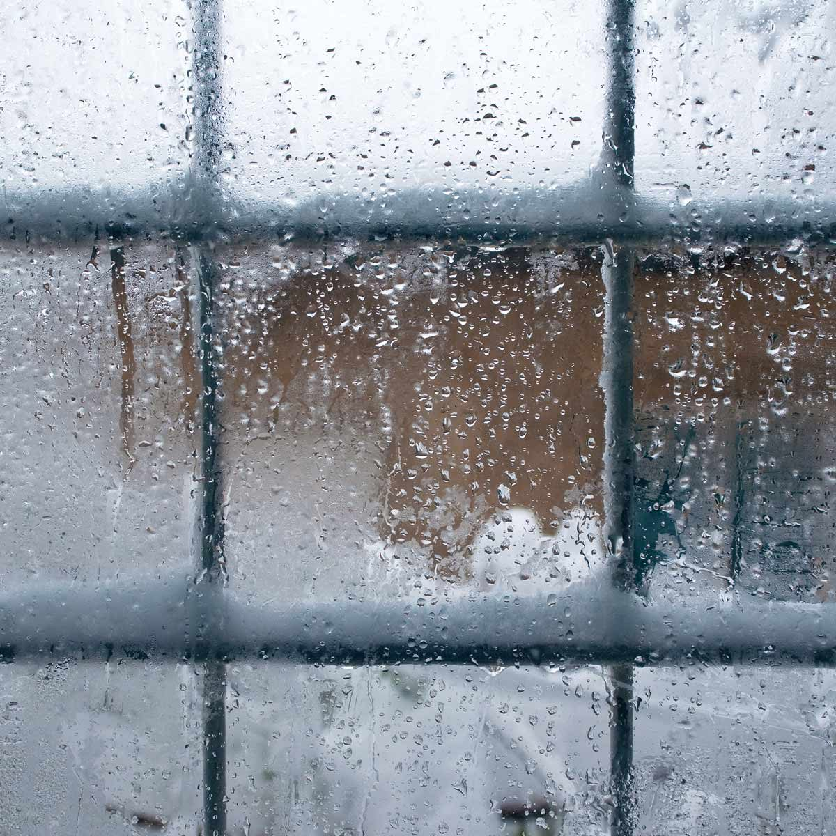 Winter window, drops of water and snowflakes on a window panel