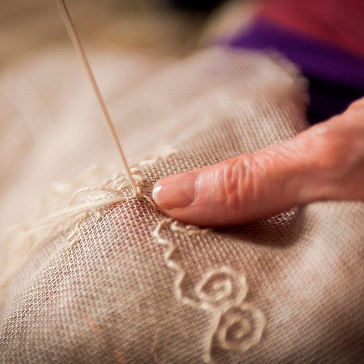 Woman sews on burlap