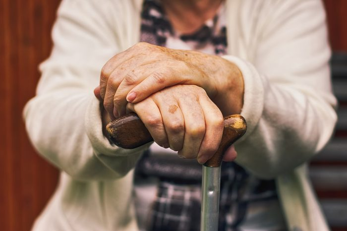 Senior woman sitting outside on a wooden bench and rests. Hands of a woman pensioner holding a walking stick.