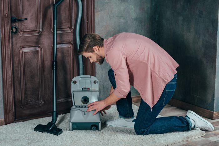 side view of young man fixing broken vacuum cleaner at home