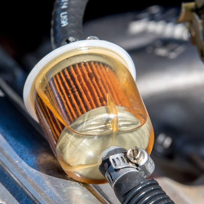 A fuel filter in a car. Gasoline can be seen in the filter. Closeup view.