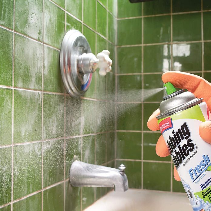 Man sprays cleaning product on shower tile