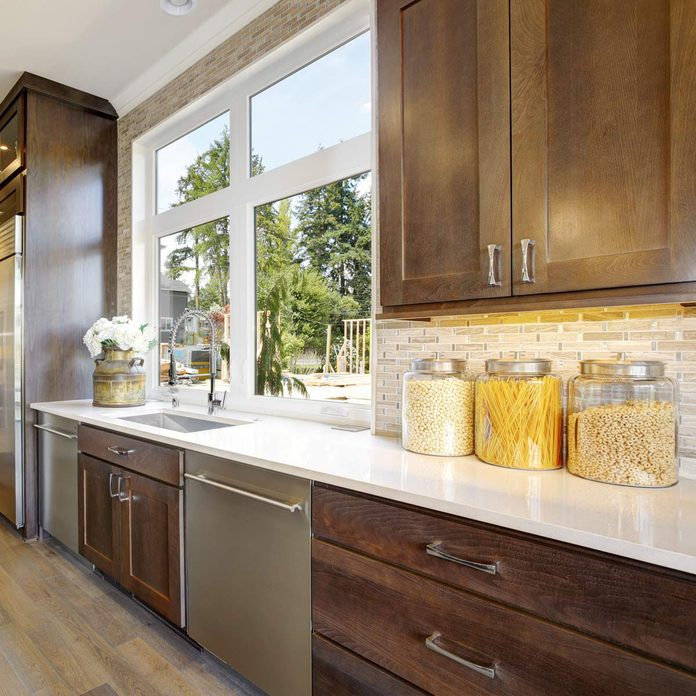 Lovely-kitchen-features-wood-cabinets-fitted-with-high-end-appliances-paired-with-a-white-quartz-countertop-fitted-with-a-sink-and-a-gooseneck-faucet-and-mosaic-backsplash