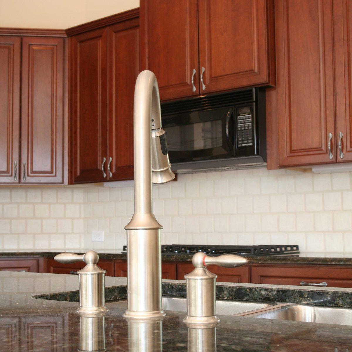 White-tile-kitchen-backsplash-set-among-dark-cabinets-and-black-granite-countertop