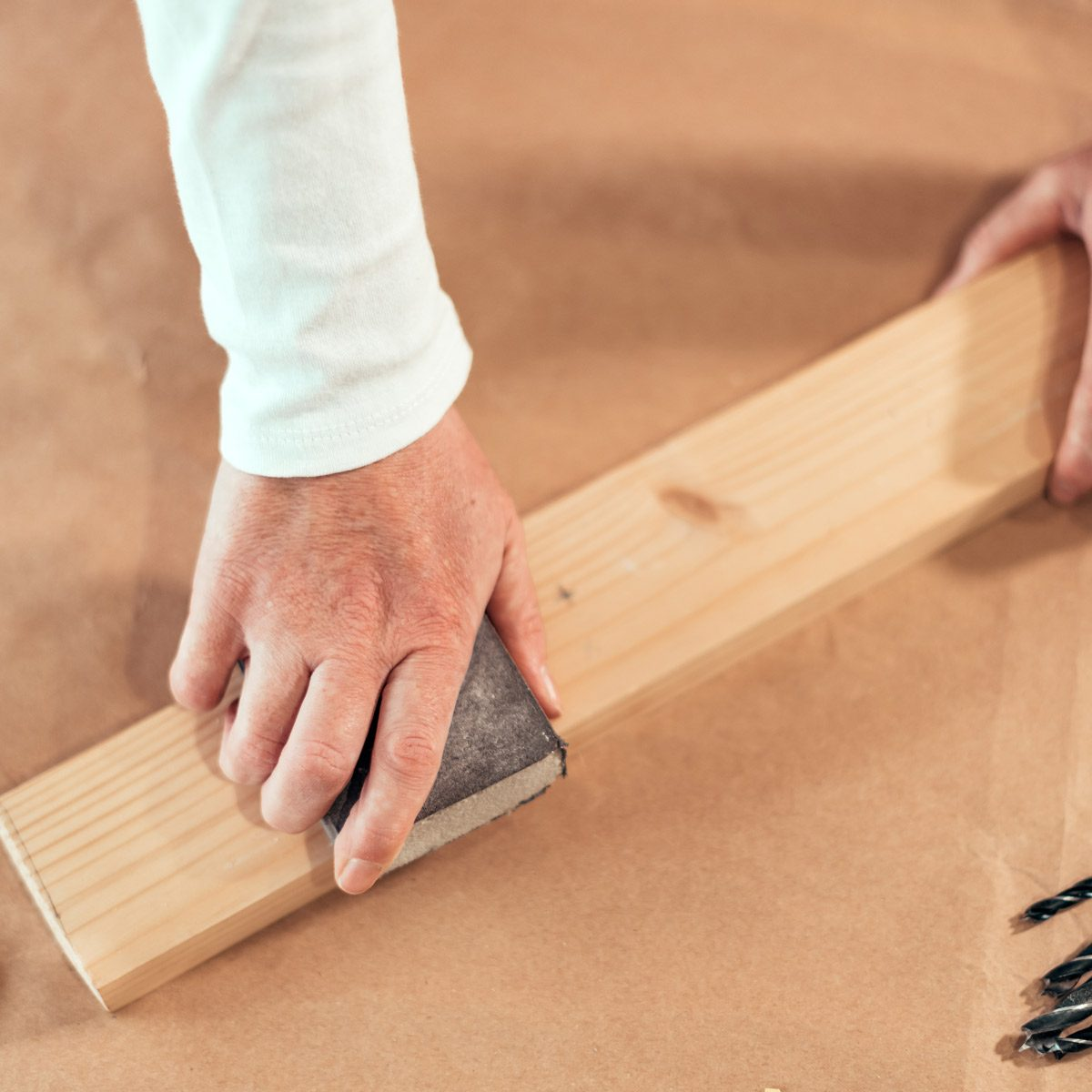 sanding wood plank with sanding sponge