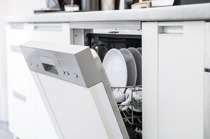 Open dishwasher with clean dishes after washing