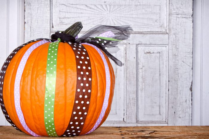 A pumpkin decorated with ribbon with aged door panel for background
