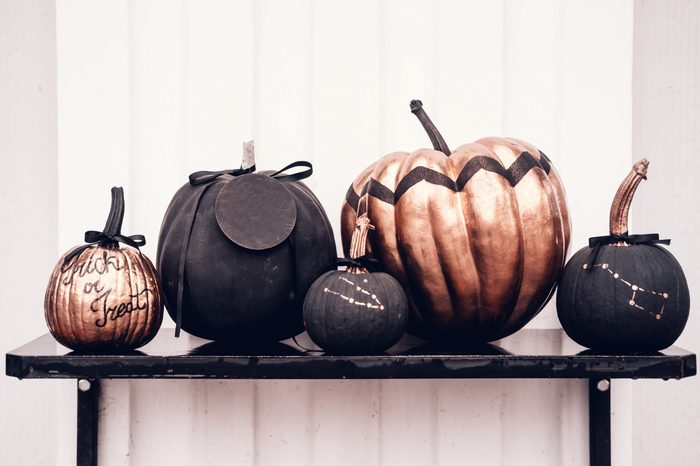 Black and rose cold colored pumpkins against white wall. Copy space