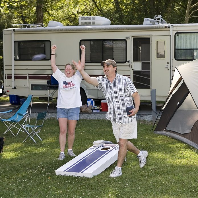 Husband and wife playing cornhole beanbag toss game at Mounds State Park in Anderson, Indiana.