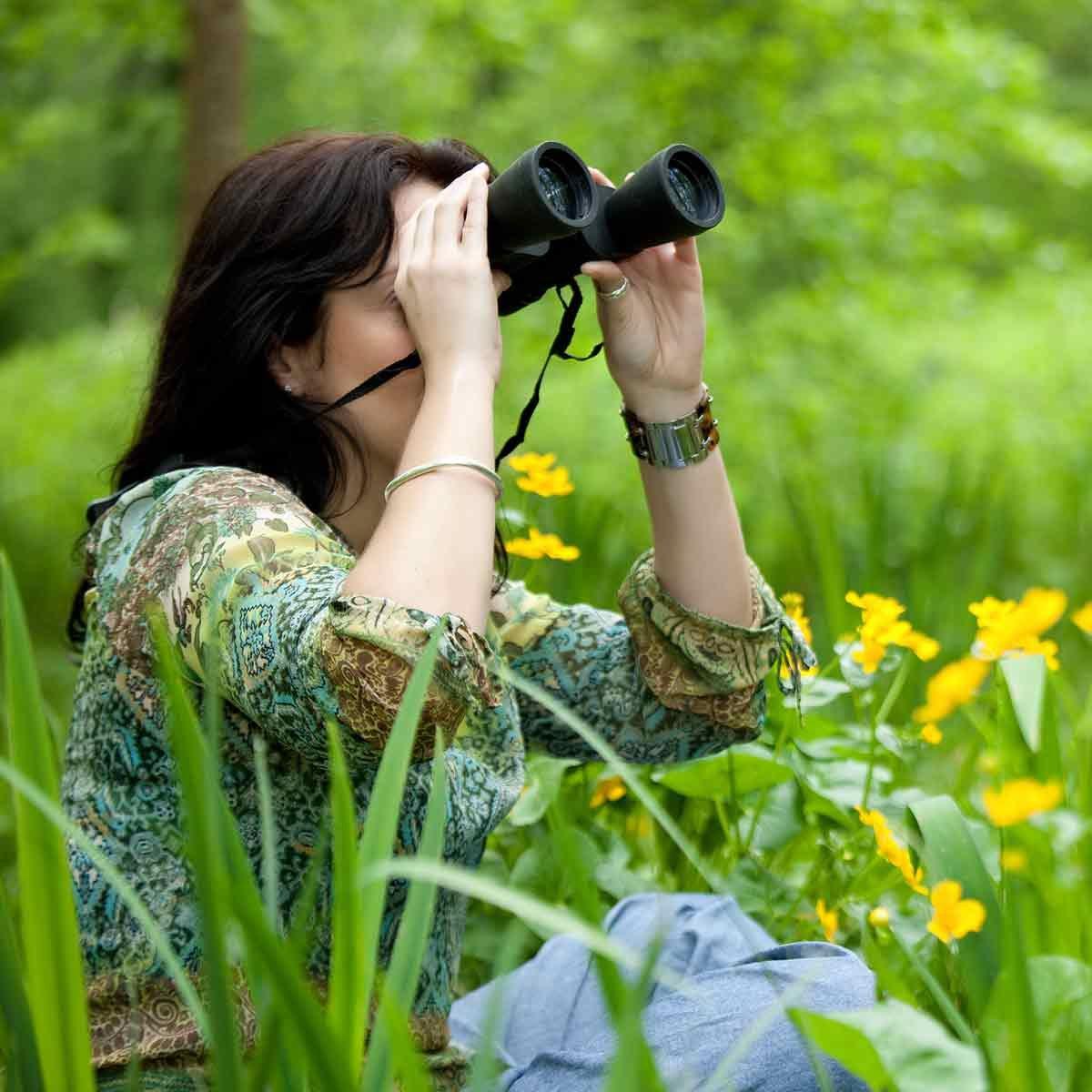 Woman-watches-birds-through-binoculars